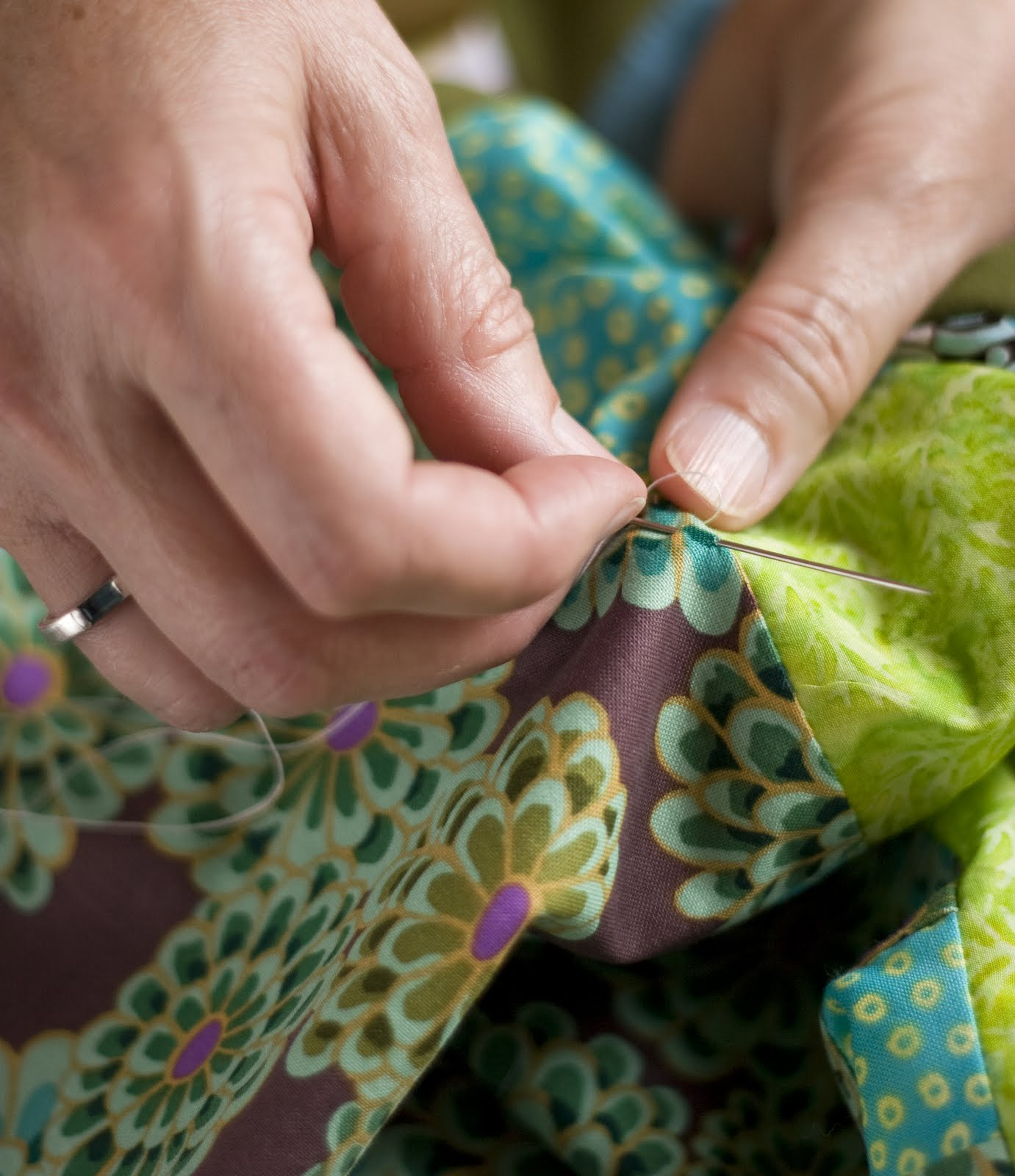 Hand stitching a blanket.