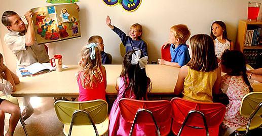 Boy raising hand during Sunday school class.