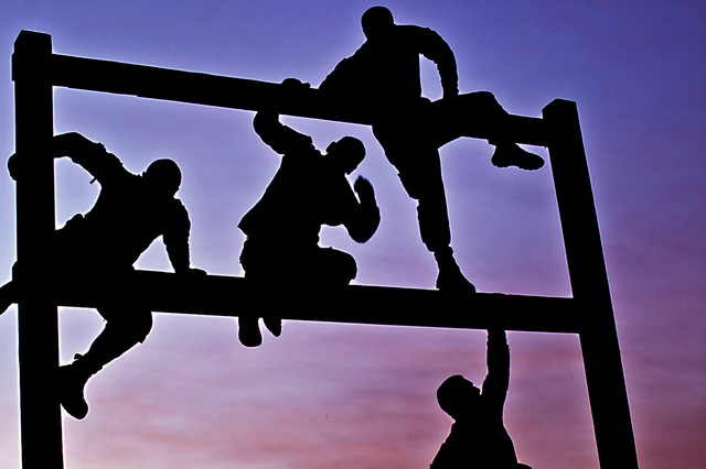 Soldiers climbing an obstacle in an obstacle course.