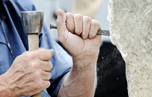 Man cutting stone with a chisel.
