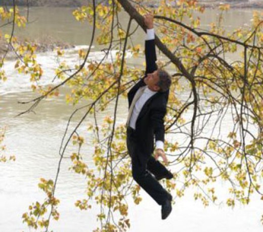 Man hanging off limb over water